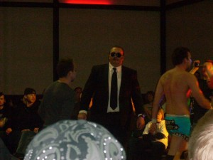 Mean Mike escorts Tommy Caliber and a victorious Cade Cassidy to the locker room